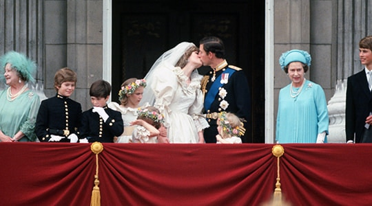 Prince Charles and Lady Diana Spencer kiss on their wedding day surrounded by members of the royal family on the balcony of Buckingham Palace.