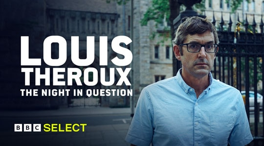 Louis Theroux stands in front of a college campus