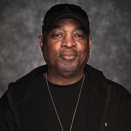 Chuck D looking into camera in front of a dark background