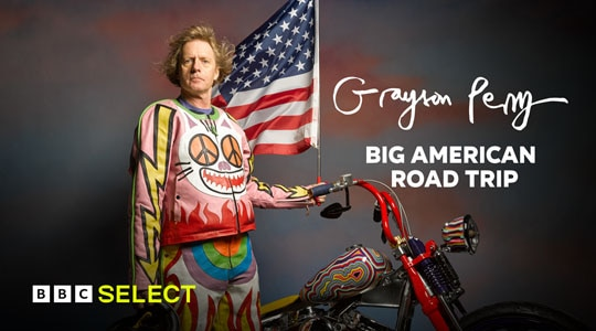 Grayson Perry standing next to a motorbike