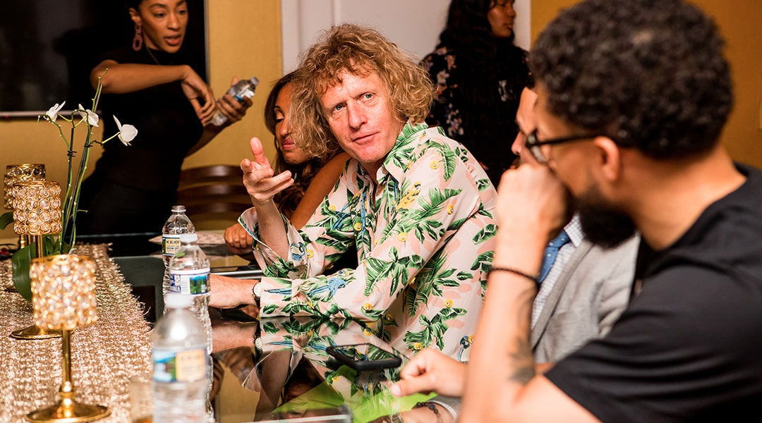 Grayson Perry sitting at a bar wearing a patterned shirt having a conversation with the individual on his left