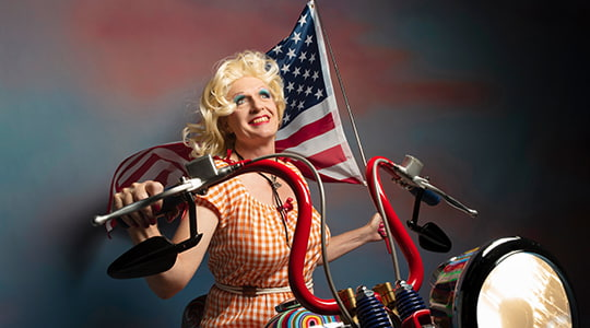 Grayson Perry sitting on a motorbike holding an American flag wearing a dress and blonde wig