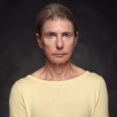 Lionel Shriver looking into camera in front of a dark background