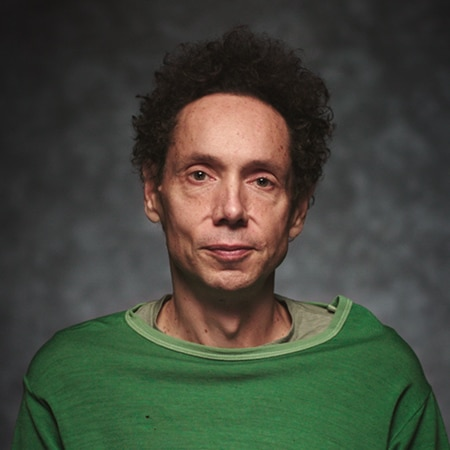 Malcolm Gladwell looking into camera in front of a dark background
