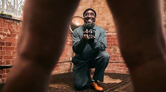 Ajamu X holding a camera with standing subject's legs in foreground