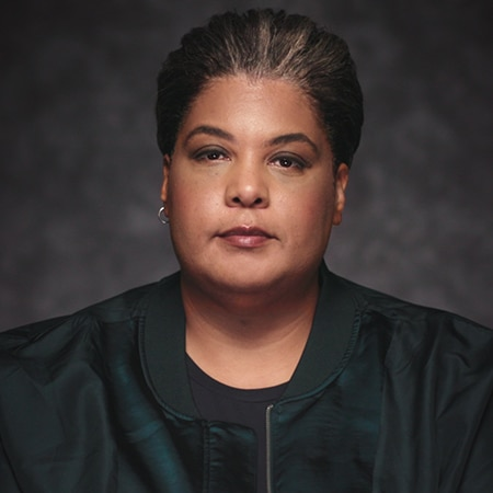 Roxane Gay looking into camera in front of a dark background
