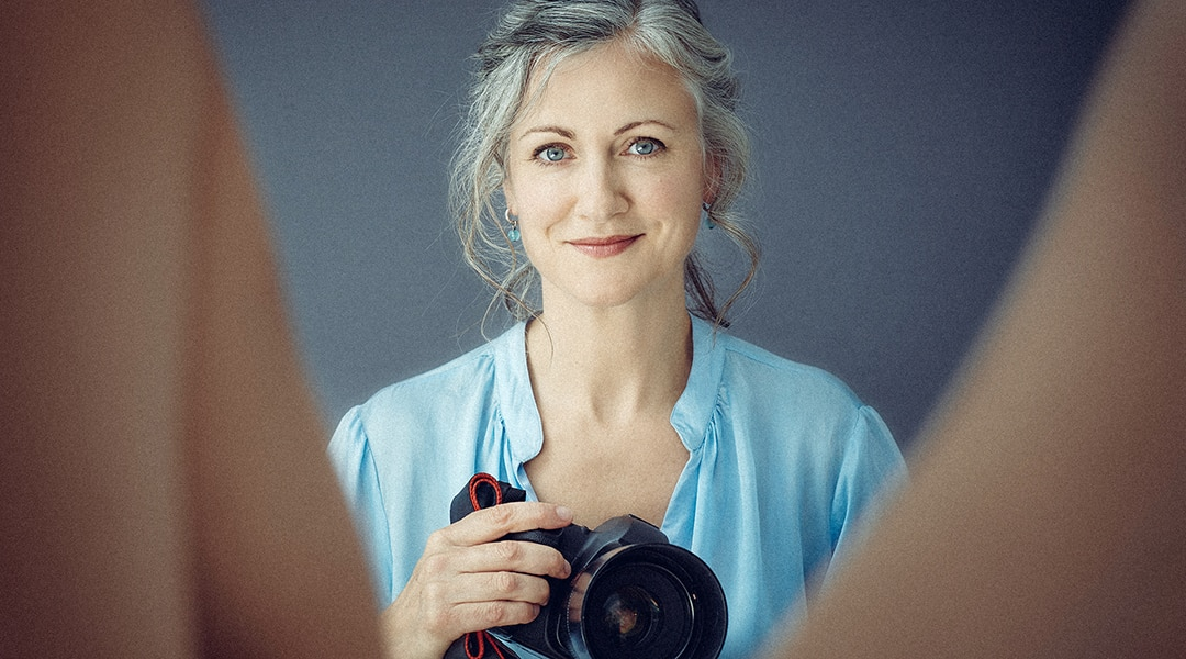 Woman wearing a light blue shirt and holding camera and looking between someone's legs