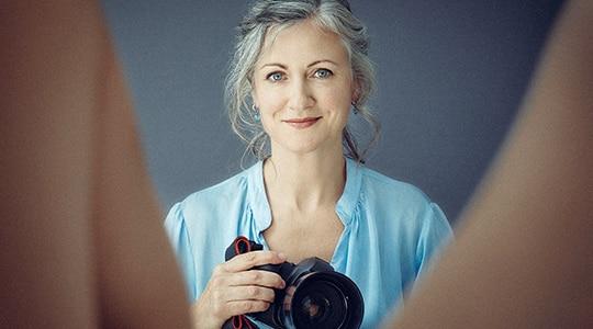 Woman wearing a blue shirt holding digital camera