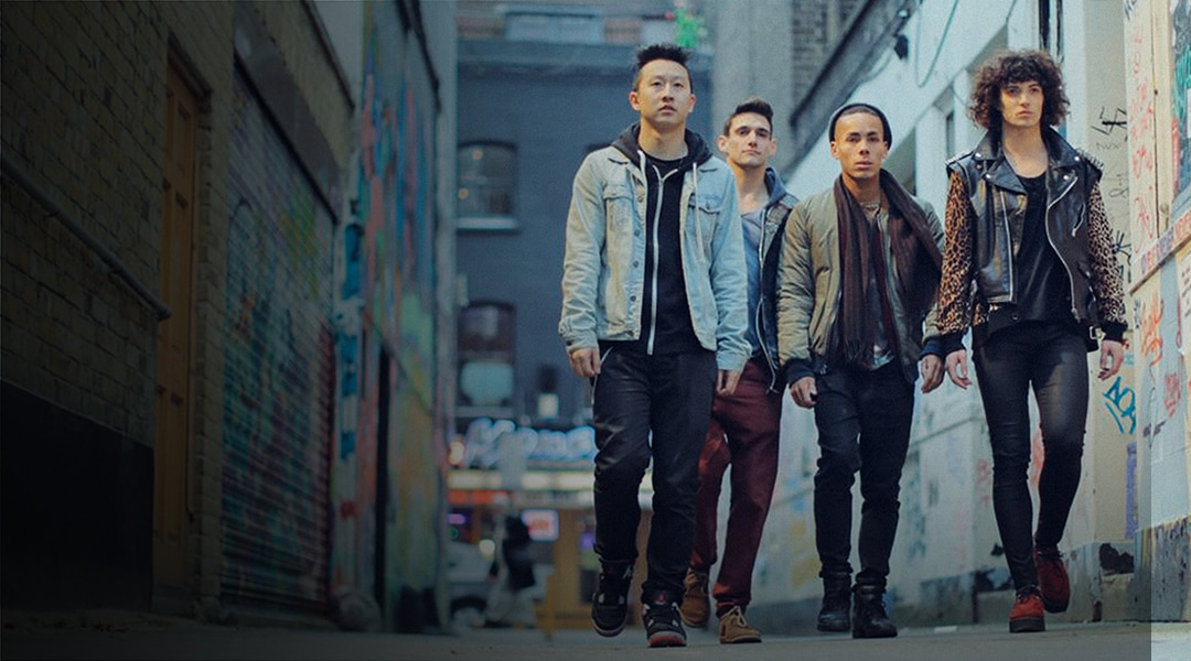 Four individuals walking down a graffiti-laden street wearing jackets