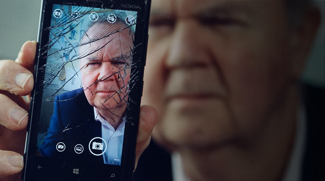 British Journalist Ian Hislop holds up a smashed phone screen with his face on the screen