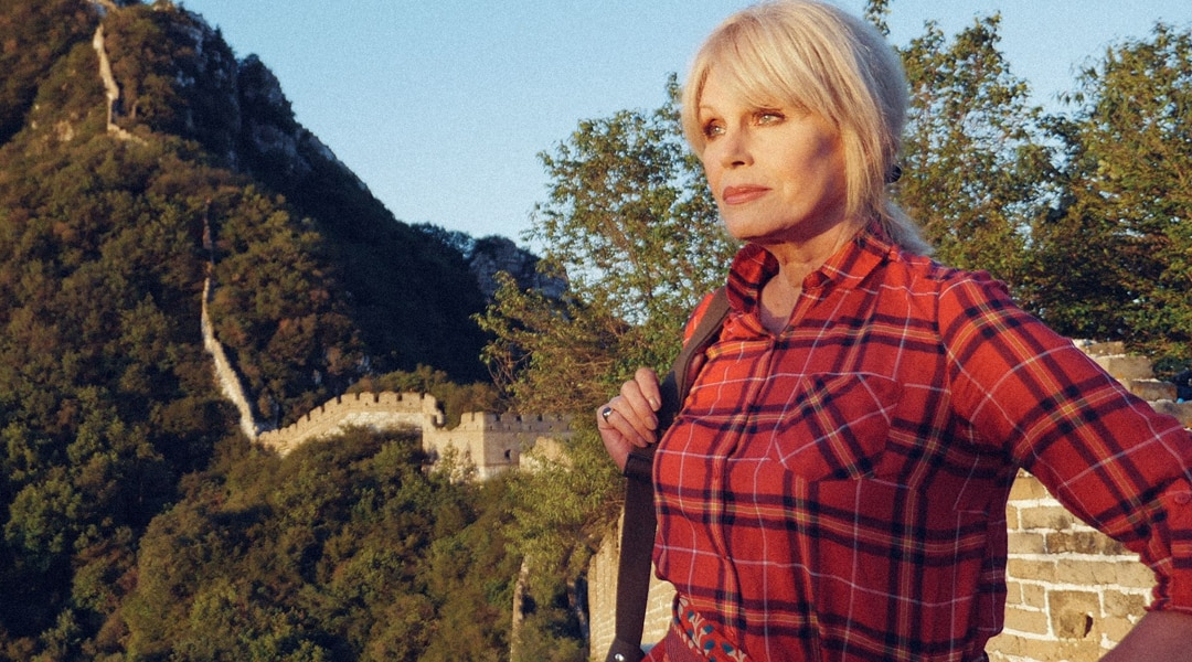 Joanna Lumley looks into the distance wearing a red checked shirt