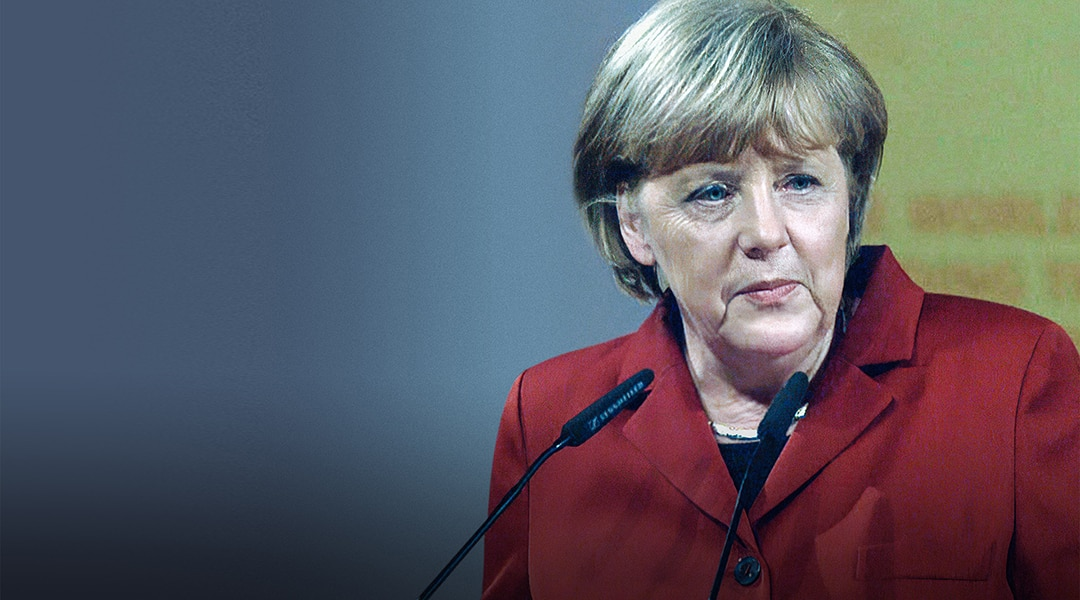 Germany's Chancellor Angela Merkel wearing a red blazer and speaking into a microphone