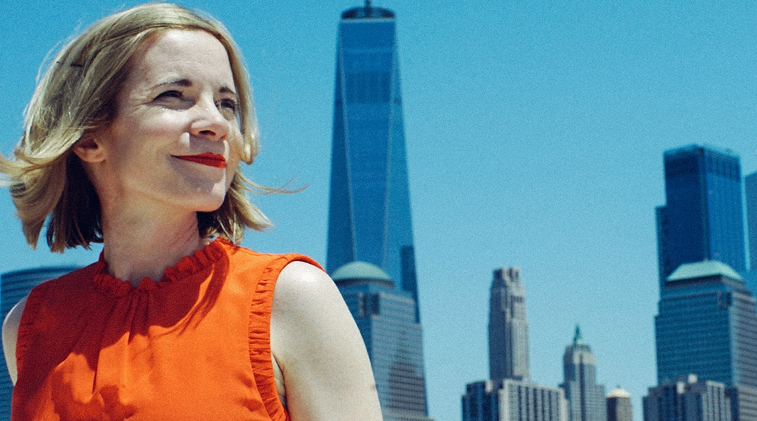 Historian Lucy Worsley looks into the distance wearing an orange dress with a skyscraper backdrop