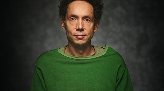 Malcolm Gladwell wears a green t-shirt in a studio for his Select Take