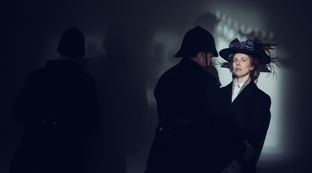 Women in large black hat and black coat being approached by a policeman