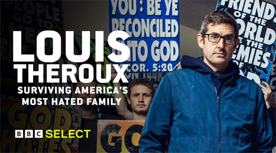 Louis Theroux stands in front of members of the Westboro Baptist Church, holding protest placards