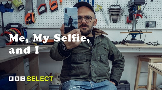 A man taking a selfie in a workshop