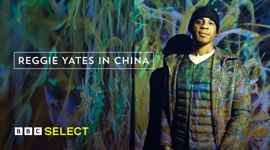 Reggie Yates stands in front of an abstract projected background