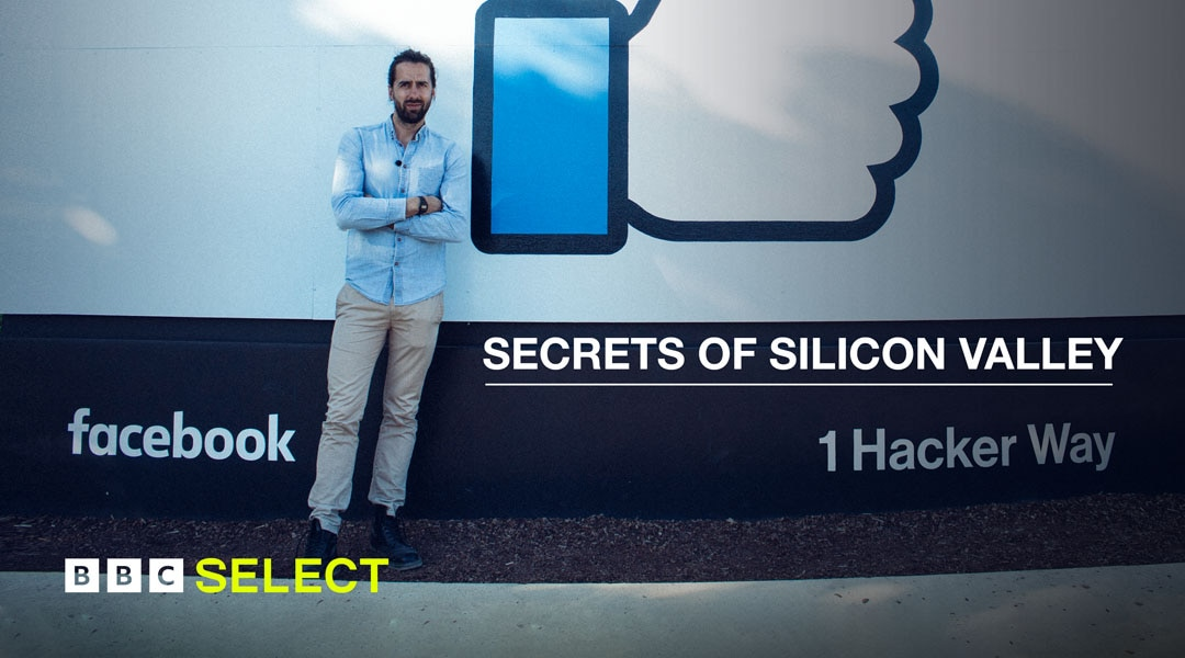 British author and journalist Jamie Barlett stands in front of the Facebook logo and 'like' sign