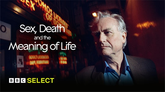 Evolutionary biologist Richard Dawkins wears a blue shirt and brown blazer